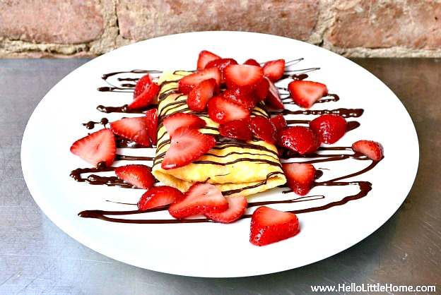 A plate of strawberry crepes with cream cheese filling.
