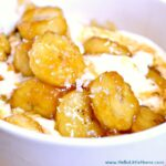 Closeup of caramelized bananas served over a bowl of ice cream.