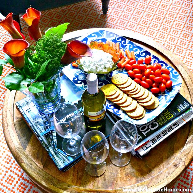 A coffee table set with Blue Cheese Spread, veggies, and crackers, and white wine.