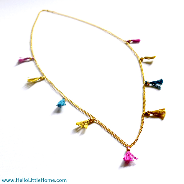 A gold necklace with tassels on a white background.