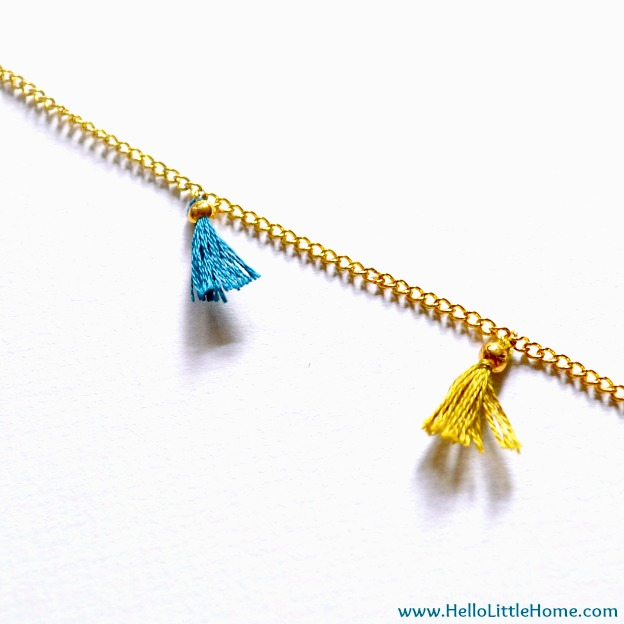 Closeup of tassels on gold chain.
