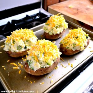 Twice Baked Potatoes topped with cheddar cheese on a baking sheet.