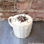 A mug of dark, rich hot chocolate flavored with espresso and served with whipped cream and chocolate sprinkles.
