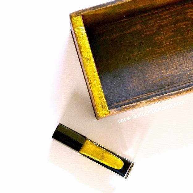 Applying gold nail polish to the edge of the shadow box.