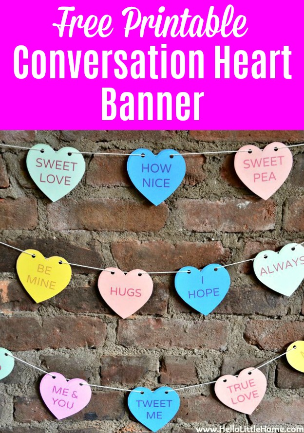 A DIY Conversation Heart Banner hanging on a brick wall.