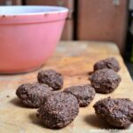 No Bake Chocolate Cookies on a cutting board with a mixing bowl in the background.