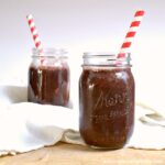 Two Berry Green Smoothies in Mason Jars with Straws.