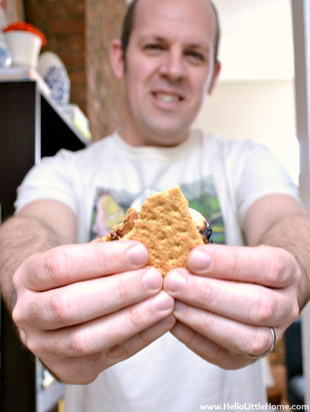 A man holding out an Indoor S'more in front of himself.