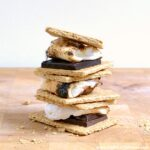 Three Indoor S'mores with different kinds of chocolate on a wood board.