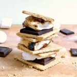A stack of three Indoor S'mores with chocolate and marshmallows on a cutting board.