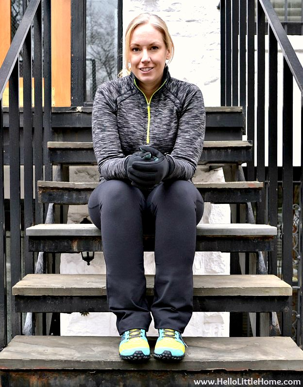 Sitting on a brownstone stoop in exercise clothes.