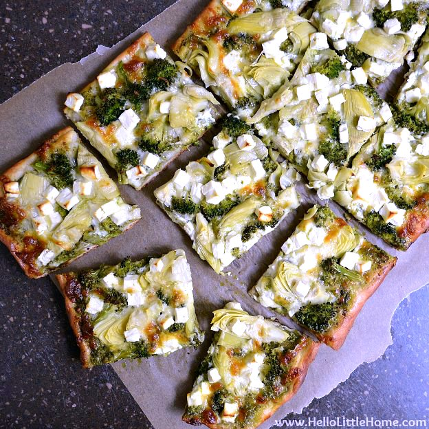 Green Pizza with Pesto, Feta, Artichokes & Broccoli ... a delicious vegetarian pizza recipe! This easy veggie pizza recipe makes a great weeknight dinner idea! This homemade Green Pizza recipe is packed with healthy toppings and tons of flavor. Make this easy vegetarian pizza recipe tonight … it's perfect for Meatless Monday or any night! | Hello Little Home #pizza #pizzarecipe #vegetarian #vegetarianrecipes #veggies #vegetables #greenpizza #veggiepizza #feta #pesto #artichokes #broccoli