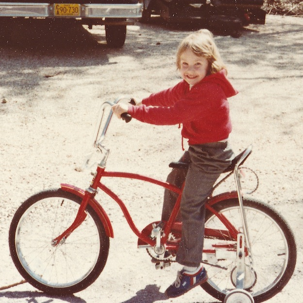 A little girl riding a bike.
