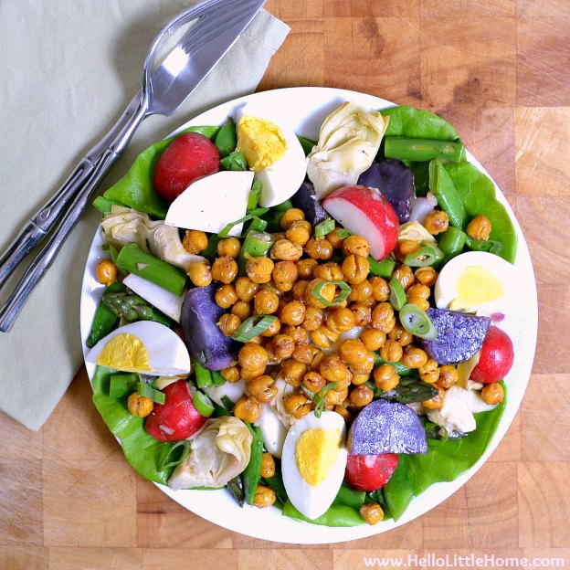A lettuce, veggie, and chickpeas salad served on a white plate.