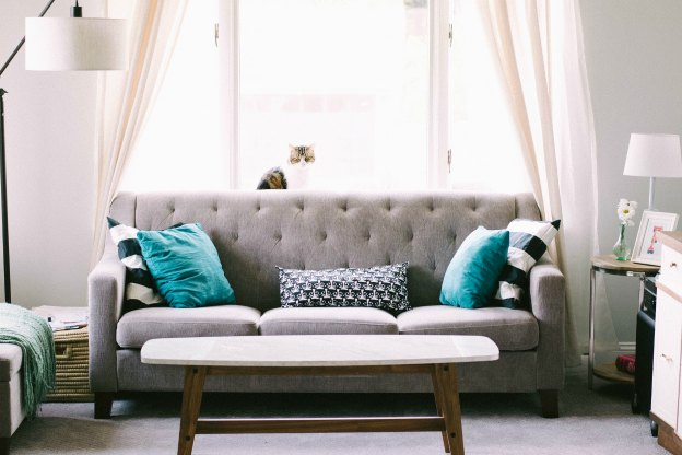 A bright living room with a couch and two chairs.