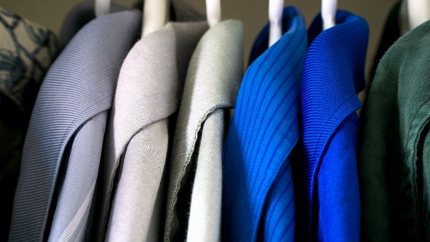 Coats hanging in an organized closet.