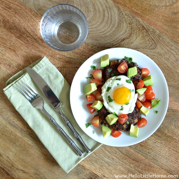 Two Spicy Black Bean Cakes topped with a Fried Egg, Avocado & Tomato