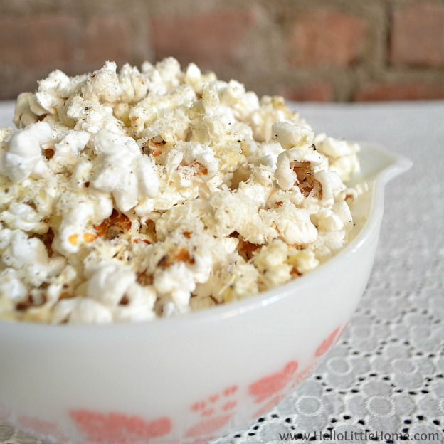A bowl of popcorn topped with parmesan cheese.