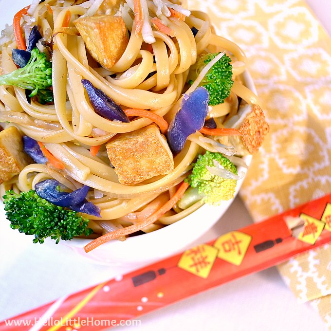Close up of a bowl of tofu lo mein with napkin and chopsticks.