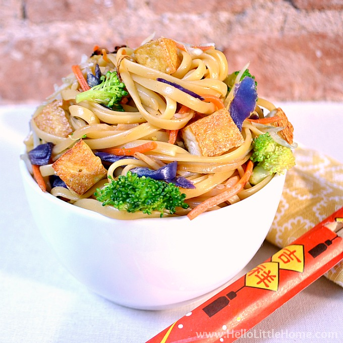 A bowl of veggie lo mein, a napkin, and a pair of chopsticks.