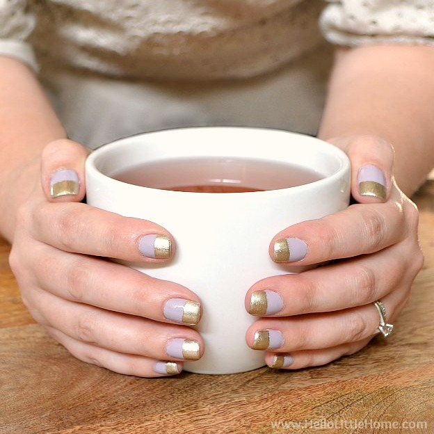 Hands with easy Wide Stripe Nail Art holding a coffee mug.