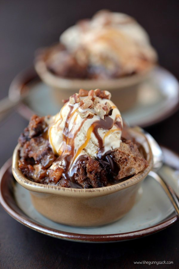 A Bowl of Slow Cooker Chocolate Turtle Sundae topped with ice cream.
