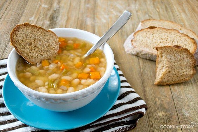 A bowl of Slow Cooker Italian Vegetarian Bean Soup on a wood table.