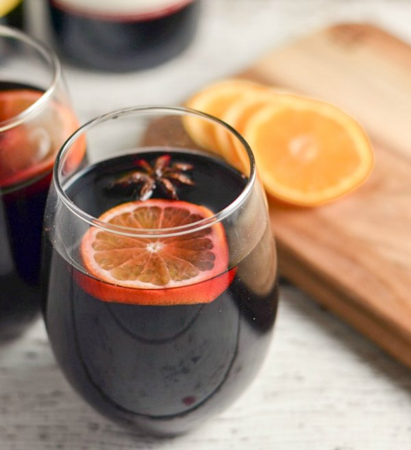 Wine glasses filled with Slow Cooker Mulled Wine and topped with orange slices.