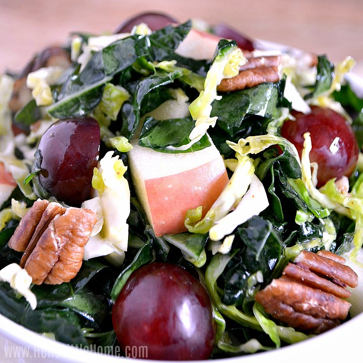 Closeup photo of kale salad with shredded brussels sprouts, apples, grapes, and pecans.