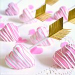 Pink and white heart shaped cake pops on a white doily.