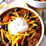 Two bowls of Roasted Vegetable Quinoa Chili with napkins and spoons on a wood table.