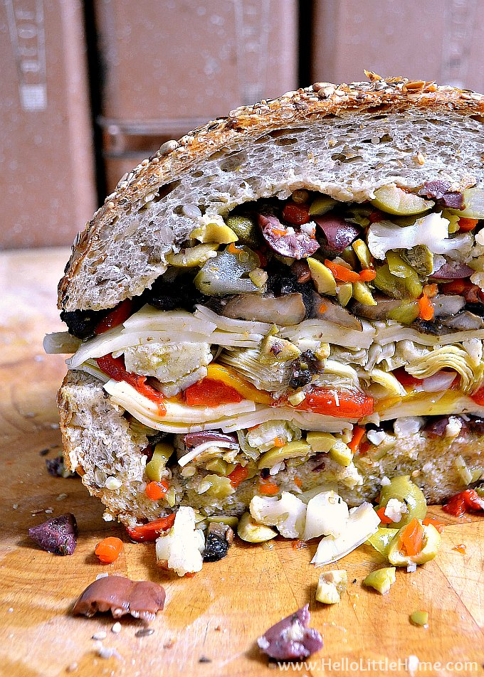 Closeup of the inside of a vegetarian muffaletta sandwhich filled with vegetables, homemade olive salad, and provolone cheese.
