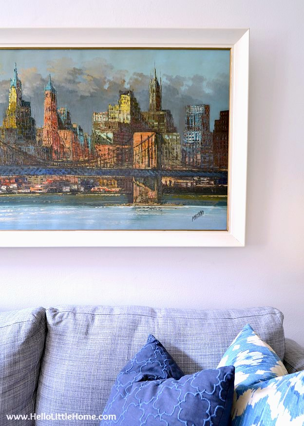 A painting of NYC in a white frame over a couch.