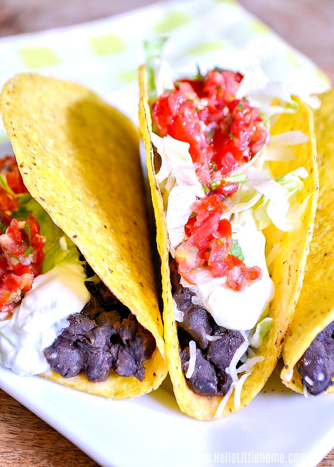 Crunchy Black Bean Tacos topped with sour cream, lettuce, and fresh salsa.