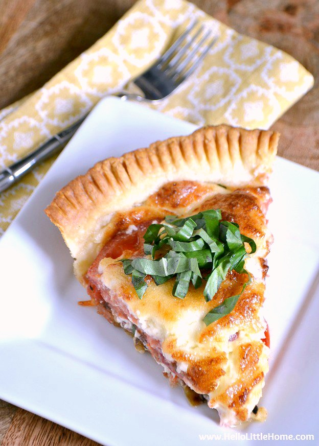 Savory Tomato, Feta, and Basil Pie ... a vegetarian savory pie that's a delicious twist on the classic Southern tomato pie recipe! Bursting with fresh summer flavors, you'll want to enjoy this easy tomato pie all season long! | Hello Little Home