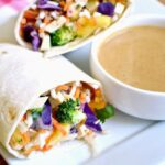 Closeup of crunchy vegetable wraps on a plate with peanut sauce.