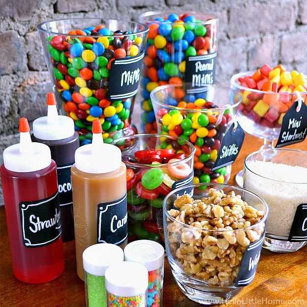 Syrups, candy, and toppings arranged together on a table.