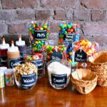 Ice Cream Sundae Bar Supplies and Toppings arranged on a wood table.