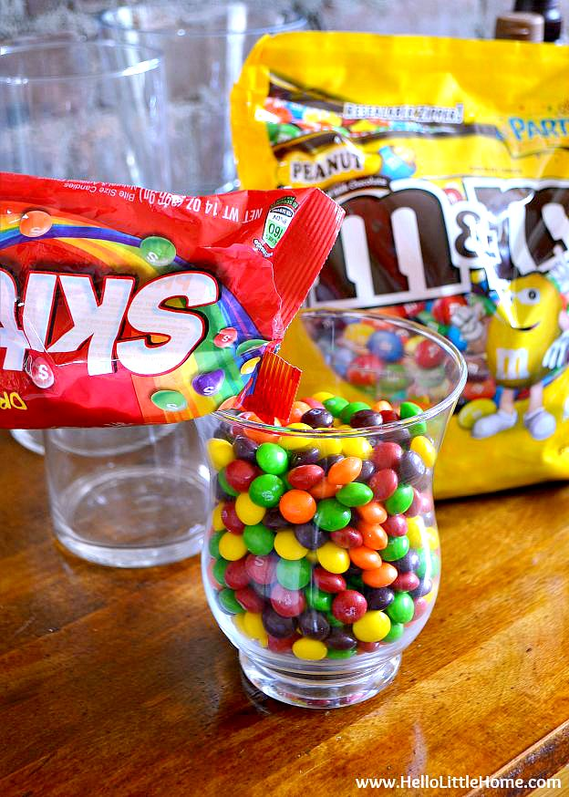Pouring a bag of candy into a glass container.