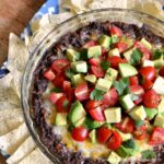 This mouth-watering Cheesy Baked Black Bean Dip has a delicious Tomato-Avocado Salsa topping ... it's the perfect game day food or great for any party! | Hello Little Home