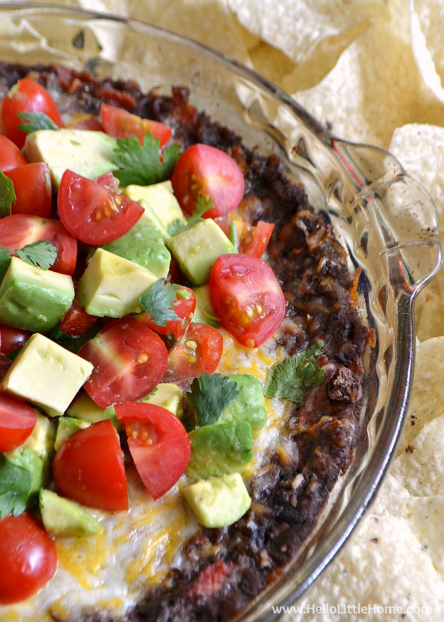 A mouth-watering Cheesy Baked Black Bean Dip that's perfect for game day or any party! This easy Baked Black Bean Dip is quick and easy to make, and it has a delicious Tomato-Avocado Salsa topping that you'll love. Serve this vegetarian dip for any party ... your guests will love it! | Hello Little Home #vegetarian #diprecipe #vegetarianrecipes #blackbeandip #beandip #blackbeans