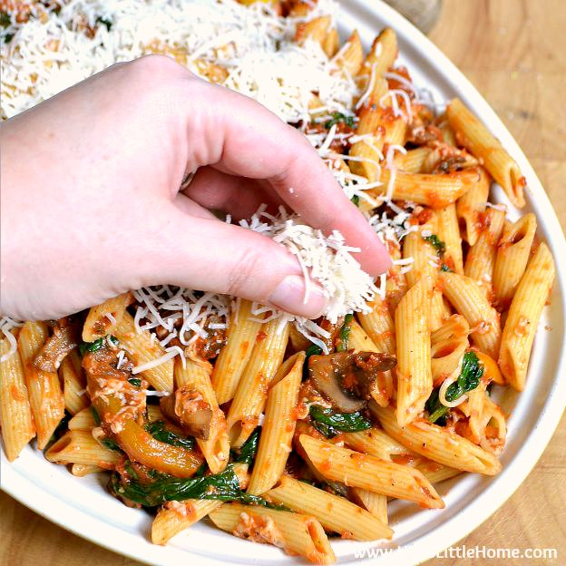 Topping Cheesy Vegetable Pasta Bake with cheese. | Hello Little Home
