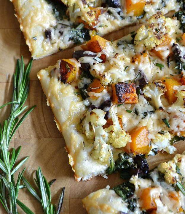 Sliced Roasted Fall Vegetable Pizza on a wood board.