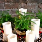 Easy DIY Christmas Centerpiece! Learn how to make a DIY Christmas Centerpiece for your table with this easy tutorial. This natural, rustic, and cheap holiday arrangement with inexpensive pine cones, burlap, candles, plaid ribbon, and fresh pine trees has a pretty farmhouse vibe and will last all season long … the perfect addition to your traditional holiday tablescape! | Hello Little Home