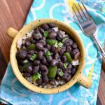 Black Beans and Rice served in a yellow bowl on a turquoise patterned napkin.