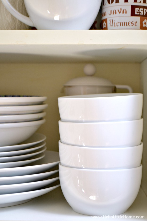A cupboard filled with white dishes.