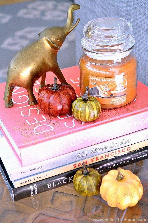Fall candle and pumpkins on a stack of books.