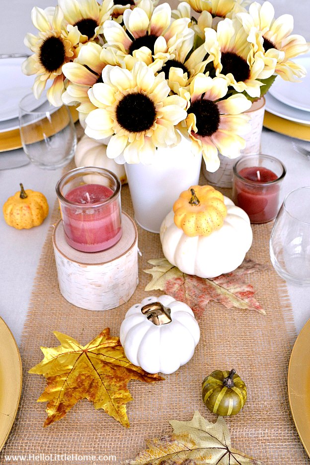 Fall Inspired Tablescape ... gorgeous fall table decor that's perfect for any autumn party or event! Beautiful fall tablescape ideas inspired by pumpkins, fall leaves, and sunflowers. These rustic, yet elegant fall table settings are simple to put together. Fragrant candles and warm gold accents make the table pop. | Hello Little Home