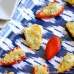 Feta stuffed mini bell peppers on a blue tray.