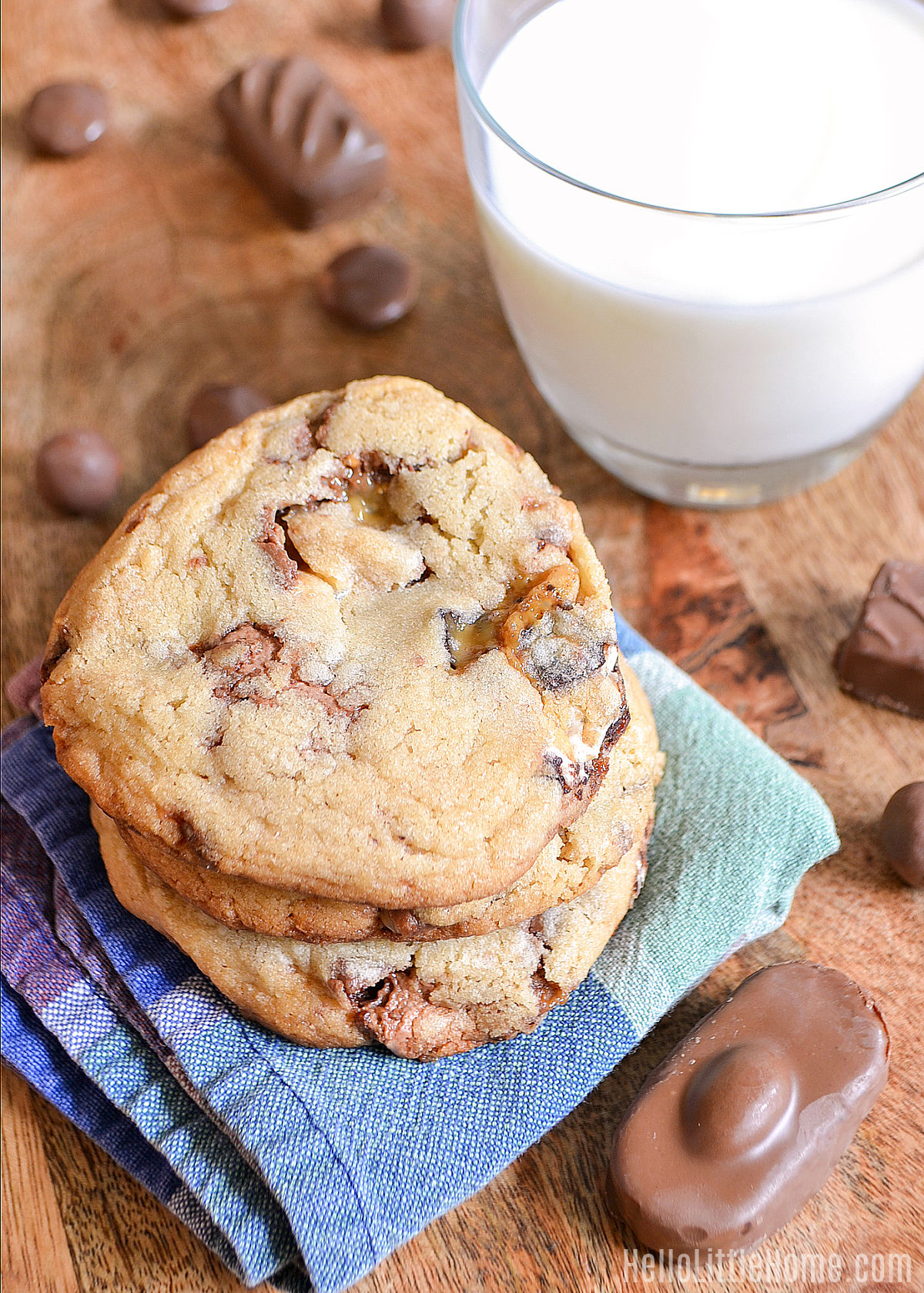 A stack of cookies, chocolate candies, and a glass of milk on a wood table.